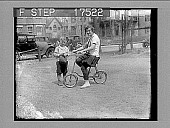 view [Woman on small-wheel bicycle with young boy standing beside her. Active no. 1751 : non-stereo photonegative.] digital asset: [Woman on small-wheel bicycle with young boy standing beside her. Active no. 1751 : non-stereo photonegative.]