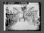 """view [Ten women in shiny uniforms saluting, with large early radio and """"Kennedy"""" banner at center.] 1792 photonegative digital asset: [Ten women in shiny uniforms saluting, with large early radio and """"Kennedy"""" banner at center.] 1792 photonegative."""