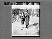 view [Man and woman walking on city sidewalk. Active no. 10185 : photonegative.] digital asset: [Man and woman walking on city sidewalk. Active no. 10185 : photonegative.]