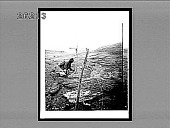 view [Kneeling black man inspecting volcanic ash after eruption, Martinique.] Active no. 6738 : half-stereo interpositive digital asset: [Kneeling black man inspecting volcanic ash after eruption, Martinique.] Active no. 6738 : half-stereo interpositive, 1902.
