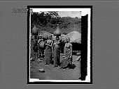 view Kikuyu women with water vessels (gourds) beside village storehouses. 10551 Interpositive digital asset: Kikuyu women with water vessels (gourds) beside village storehouses. 10551 Interpositive.
