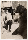 view [Male Ludar Gypsy trainer squating next to chained bear sitting and watching, b&w photoprint.] digital asset: [Male Ludar Gypsy trainer squating next to chained bear sitting and watching, b&w photoprint.]