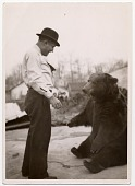 view [Male Ludar Gypsy trainer standing in front of chained bear sitting and watching, b&w photoprint.] digital asset: [Male Ludar Gypsy trainer standing in front of chained bear sitting and watching, b&w photoprint.]