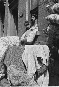 view [Rom woman and child leaning out apartment window, airing bedding--featherbeds, blankets, pillows], photoprint digital asset: [Rom woman and child leaning out apartment window, airing bedding--featherbeds, blankets, pillows], photoprint.
