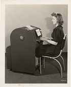 view [Woman seated in front of and typing on a Western Union Teleprinter; Black-and-white photoprint.] digital asset: [Woman seated in front of and typing on a Western Union Teleprinter; Black-and-white photoprint.]