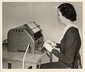view [Woman seated in front of and typing on a Western Union machine with tape coming out of side : black-and-white photoprint] digital asset: [Woman seated in front of and typing on a Western Union machine with tape coming out of side : black-and-white photoprint]
