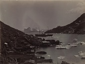 view [Wooden buildings, sheds, and platforms on the shore of a cove with icebergs and ship in background, b&w photoprint] digital asset: [Wooden buildings, sheds, and platforms on the shore of a cove with icebergs and ship in background, b&w photoprint]