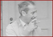 view [Groucho Marx smoking a cigar in front of his California house : black-and-white film frame.] digital asset: [Groucho Marx smoking a cigar in front of his California house : black-and-white film frame.]
