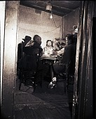 view [Four men and a woman seated at a table under a bare light bulb: photonegative.] digital asset: [Four men and a woman seated at a table under a bare light bulb: photonegative.]