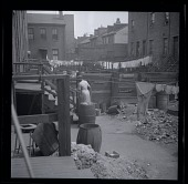 view [Woman and laundry in alley : photonegative.] digital asset: [Woman and laundry in alley : photonegative.]