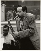 view [Jimmy Hamilton, Paul Gonsalves (foreground, playing saxophone), Bobby Boyd, valet and bandboy (background in recording booth), black-and-white photoprint,] 1956 digital asset: [Jimmy Hamilton, Paul Gonsalves (foreground, playing saxophone), Bobby Boyd, valet and bandboy (background in recording booth), black-and-white photoprint,] 1956.