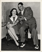 view [Beatrice Ellis; AKA Evie Ellington sitting in a chair with Duke Ellington sitting on the arm of the chair : black-and-white photoprint.] digital asset: [Beatrice Ellis; AKA Evie Ellington sitting in a chair with Duke Ellington sitting on the arm of the chair : black-and-white photoprint.]