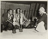 view [Duke Ellington and Paul Gonsalves with hookah and drinking tea in Ctesiphon, Iraq : black-and-white photoprint] digital asset: [Duke Ellington and Paul Gonsalves with hookah and drinking tea in Ctesiphon, Iraq : black-and-white photoprint, 1963.]