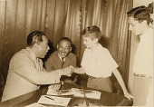 view [Duke Ellington at a USIS (United States Information Service) library, shaking hands with a boy. Location unknown, photographic print,] digital asset: [Duke Ellington at a USIS (United States Information Service) library, shaking hands with a boy. Location unknown, photographic print,] 1963.