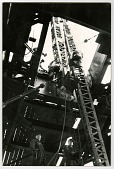 """view Jumping the derrick--moving the derrick to the next operational floor--two floors up / Empire State Building 1930 [photoprint] digital asset: """"Jumping on the derrick-moving the derrick to the next operational floor"""" [Masonite mount]"""