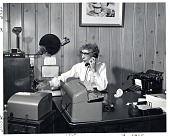 view [Mrs. Birdie Nebel, receptionist and switch board operator, at her desk in Baltimore, Maryland : black-and-white photoprint] digital asset: [Mrs. Birdie Nebel, receptionist and switch board operator, at her desk in Baltimore, Maryland : black-and-white photoprint], 1961.