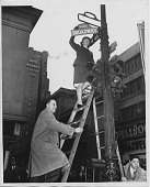 "view [Woman on ladder changing street sign to ""Donut Corner Broadway""] : [black-and-white photoprint] digital asset: [Woman on ladder changing street sign to ""Donut Corner Broadway""] : [black-and-white photoprint]"