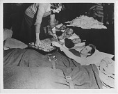 view [Woman giving donuts to injured (?) soldiers]: [black-and-white photoprint] digital asset: [Woman giving donuts to injured (?) soldiers]: [black-and-white photoprint]