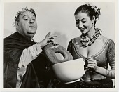 "view [Zero Mostel in ""A Funny Thing Happened on the Way to the Forum"" in costume, dunking giant donut in giant cup held by young woman: black-and-white photoprint] digital asset: [Zero Mostel in ""A Funny Thing Happened on the Way to the Forum"" in costume, dunking giant donut in giant cup held by young woman: black-and-white photoprint]"