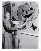 view [Blindfolded child pinning doughnut to Jack-o-Lantern's mouth : black-and-white photoprint.] digital asset: [Blindfolded child pinning doughnut to Jack-o-Lantern's mouth : black-and-white photoprint.]