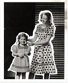 view [Woman and girl dressed in similar dresses made of doughnut print fabric : black-and-white photoprint.] digital asset: [Woman and girl dressed in similar dresses made of doughnut print fabric : black-and-white photoprint.]
