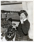 view [Young girl eating a donut standing next to a boat wheel : black-and-white photoprint.] digital asset: [Young girl eating a donut standing next to a boat wheel : black-and-white photoprint.]