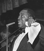 view Louis Armstrong [singing at microphone, holding handkerchief [black-and-white photoprint, black-and-white] digital asset: Armstrong, Louis; Birdland, New York City, 1956