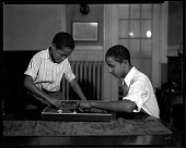 view [Two African American boys playing baseball table game] [cellulose acetate photonegative] digital asset: [Boys playing board game. Black-and-white cellulose acetate photonegative].