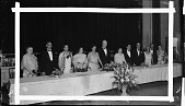 view [Group of men and women in evening dress standing behind a table, ca. 1930-1940 : cellulose acetate photonegative, banquet camera format, banquet camera format] digital asset: [Group of men and women in evening dress standing behind a table, ca. 1930-1940 : cellulose acetate photonegative, banquet camera format, banquet camera format].