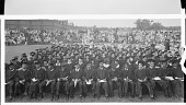 view [Seated group of graduates in academic robes with spectators in bleachers behind, Howard University : cellulose acetate photonegative, banquet camera format] digital asset: [Seated group of graduates in academic robes with spectators in bleachers behind, Howard University : cellulose acetate photonegative, banquet camera format].