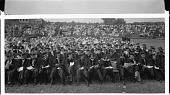 view [Seated group of graduates in academic robes with spectators seated behind and in bleachers, Howard University : cellulose acetate photonegative, banquet camera format] digital asset: [Seated group of graduates in academic robes with spectators seated behind and in bleachers, Howard University : cellulose acetate photonegative, banquet camera format].