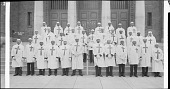 view [Posed group of men standing in three rows on the exterior steps of a building, dressed in white coats and hats with crosses on them, ca. 1930-1940 : cellulose acetate photonegative, banquet camera format] digital asset: [Posed group of men standing in three rows on the exterior steps of a building, dressed in white coats and hats with crosses on them, ca. 1930-1940 : cellulose acetate photonegative, banquet camera format].