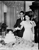 view Miss Lewis Johnson [cutting cake]. [Black-and-white photonegative] digital asset: Miss Lewis Johnson [cutting cake]. [Black-and-white photonegative, ca. 1940s.]
