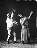 view [Robert Taylor holding horn and tambourine, with female partner] [acetate film photonegative] digital asset: [Robert Taylor holding horn and tambourine, with female partner] [acetate film photonegative].