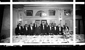 view [Armond W. Scott Kappa Alpha Psi testimonial dinner: 12 men, some in black-tie formal attire, standing behind table, with a fan mounted above the door behind them] [acetate film photonegative] digital asset: [Armond W. Scott Kappa Alpha Psi testimonial dinner: 12 men, some in black-tie formal attire, standing behind table, with a fan mounted above the door behind them] [acetate film photonegative, ca. 1935.]