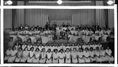 view [Cardozo High School orchestra, on stage, chorus sitting below : panoramic acetate film photonegative] digital asset: [Cardozo High School orchestra, on stage, chorus sitting below : panoramic acetate film photonegative, ca. 1934-1935.]