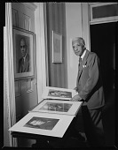 view [Addison N. Scurlock inspecting some of his portraits : acetate film photonegative and prints] digital asset: [Addison N. Scurlock inspecting some of his portraits : acetate film photonegative and prints], 1955.