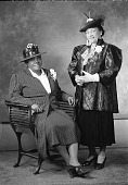 view [Mary McLeod Bethune seated in chair, full length, wearing hat and striped suit with corsage, with another woman standing beside her : acetate film photonegative,] digital asset: [Mary McLeod Bethune seated in chair, full length, wearing hat and striped suit with corsage, with another woman standing beside her : acetate film photonegative,] June 1939.