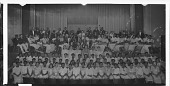 view [Orchestra on stage and group of girls seated in rows in front of stage : acetate film photonegative, banquet camera format.] digital asset number 1