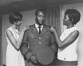 view [Captain Rhodes, U.S. Army Infantry, with two women admiring his uniform : photoprint, ca. 1970.] digital asset number 1