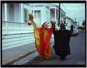 view Photo of two vejigantes walking on the street wearing the traditonal outfit of the Carnival of Ponce. One of the vejigantes wears colors orange and yellow while the other wears black. digital asset: Photo of two vejigantes walking on the street wearing the traditonal outfit of the Carnival of Ponce. One of the vejigantes wears colors orange and yellow while the other wears black.