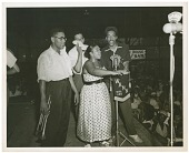 view [Vanetta Dillard performs in front of a WANN microphone, three men on stage with her, and large audience looking on.] [Black-and-white photoprint] digital asset: [Vanetta Dillard performs in front of a WANN microphone, three men on stage with her, and large audience looking on.] [Black-and-white photoprint].