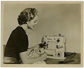 view [Woman using the Brother Pacesetter sewing machine : black-and-white photoprint] digital asset: [Woman using the Brother Pacesetter sewing machine : black-and-white photoprint, ca. 1950s].
