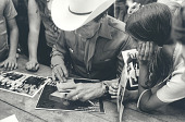 view Ernest Tubb signing autographs digital asset: Ernest Tubb (1914-1984), man signing autographs, photographs and record album.