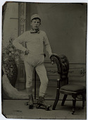 view Man in diaper and rollerskates digital asset: Tintype studio portrait of a man wearing rollerskates and a diaper