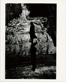 view Man Walking with his Shadow digital asset: Man walking on wet pavement, photograph by Ray K. Metzker