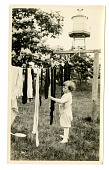view Young child standing next to clothesline digital asset number 1