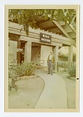 """view man standing in front of building with """"Weibel Hacienda"""" on sign overhead digital asset: man standing in front of building with 'Weibel Hacienda' on sign overhead"""