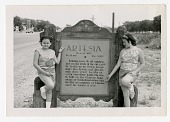 """view two girls next to """"Artesia"""" sign digital asset: two girls next to 'Artesia' sign"""