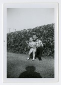 view Young boy with man next to hedge digital asset: Young boy with man next to hedge